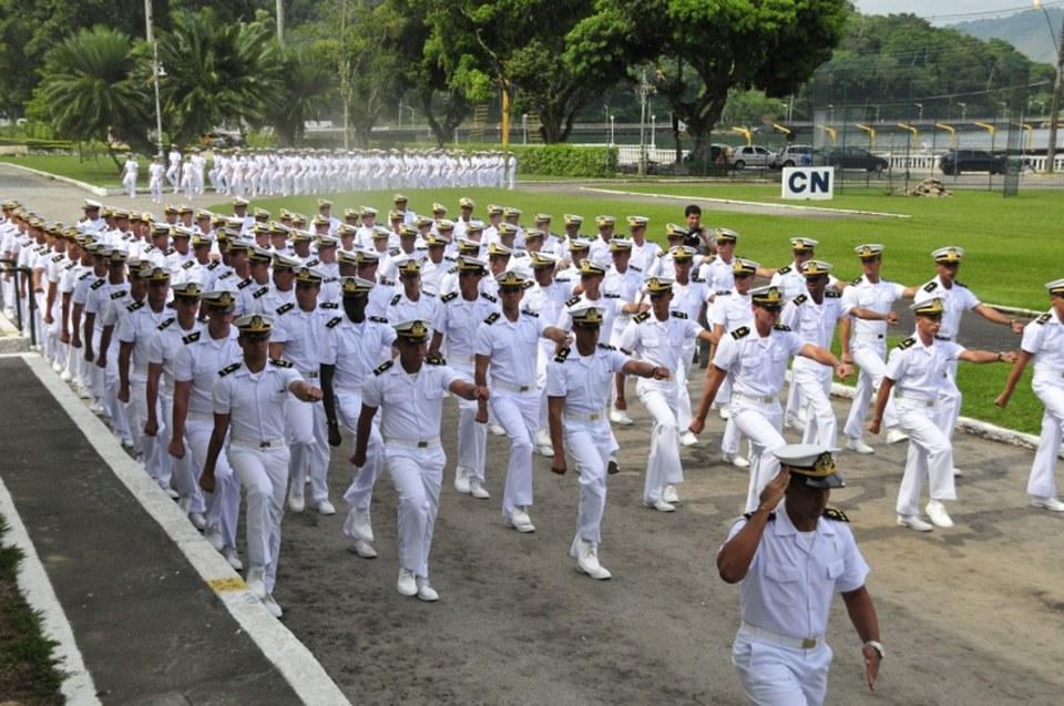 Para ilustrar a atuação dos profissionais que forem selecionados no concurso público, a foto mostra diversos homens com uniforme da Marinha do Brasil marchando