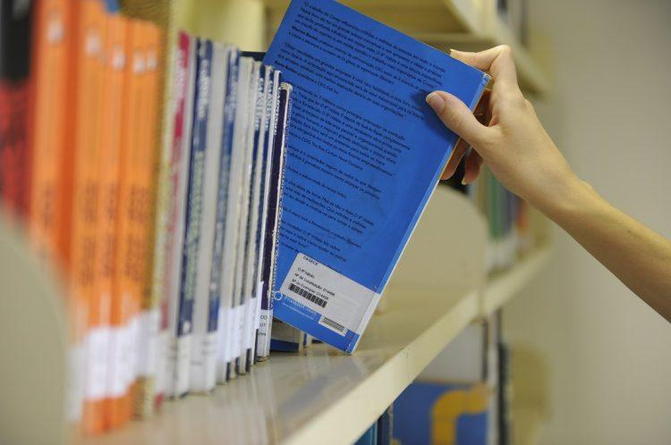 Pessoa retirando livro de capa azul da estante de uma biblioteca de metal