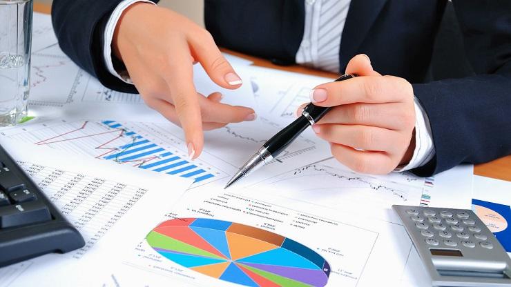 Mãos segurando caneta, calculadora e outros objetos relacionados a finanças