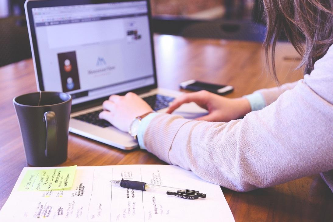 Mãos de uma mulher que utiliza notebook. Ao lado do computador, uma caneca preta e um caderno com uma caneta em cima.