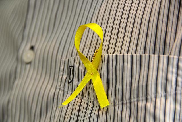 Detalhe de faixa amarela, símbolo da campanha Setembro Amarelo, presa ao bolso de uma camiseta social com fundo branco e listras pretas