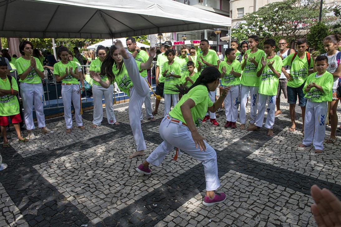 Em roda, grupo assiste a duas mulheres jogando capoeira