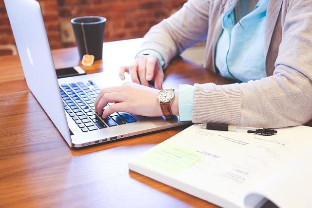 Detalhes das mãos de uma mulher que está usando o notebook