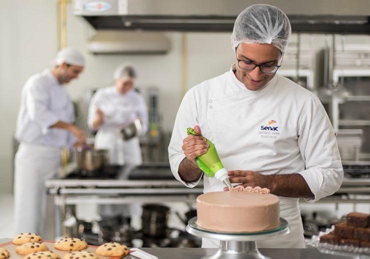 Instrutores do Senac confeitando um bolo