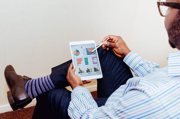 Funcionário trabalhando com auxílio de uma tablet para Trade Marketing. A ferramenta mostra gráficos coloridos.