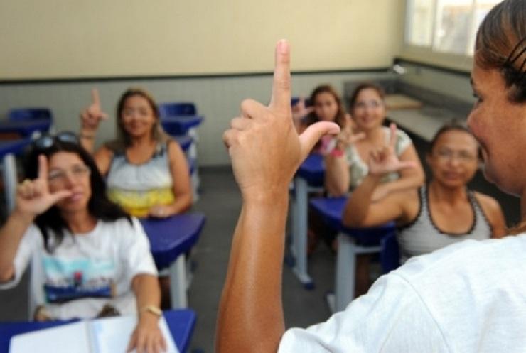 Pessoa ensinando libras aos alunos em uma sala de aula