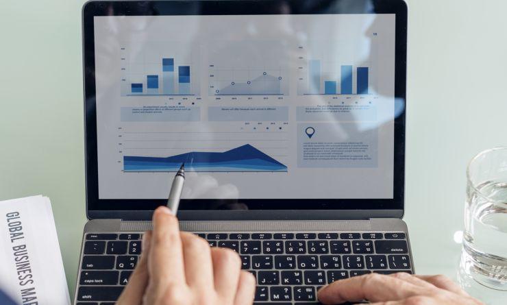 Mão com uma caneta, apontando para imagem de gráfico na tela de notebook
