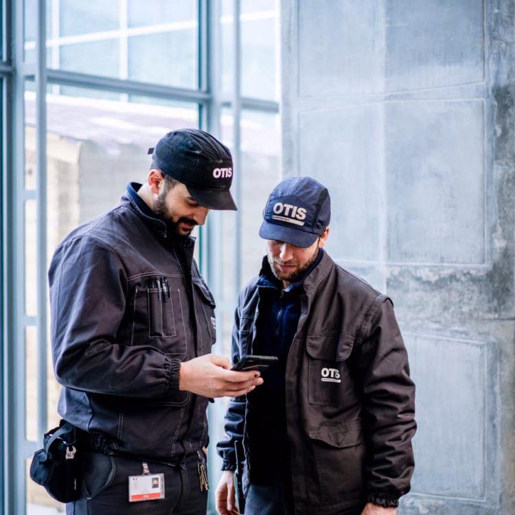 Dois funcionários conversando e vestidos com uniforme da Otis