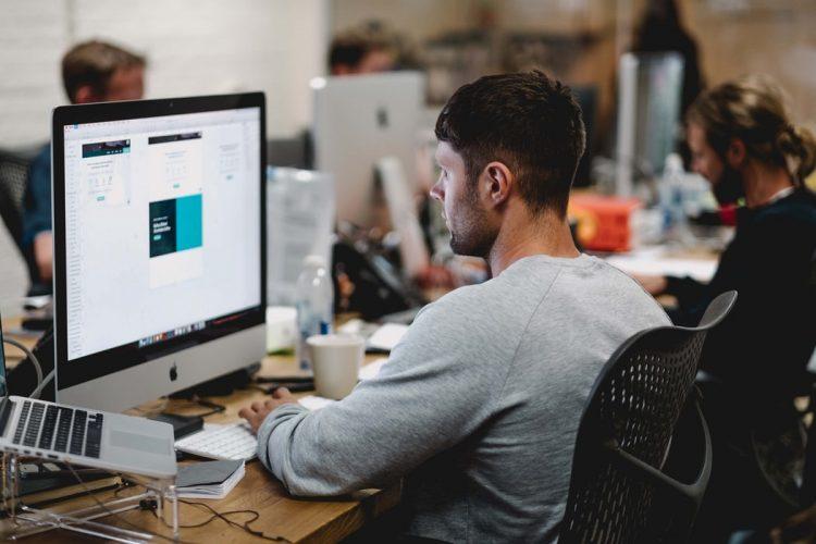 Homem de costas e sentado em frente a computador