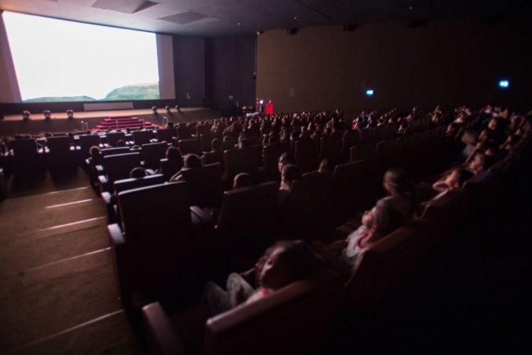 Pessoas assistindo a um filme em uma sala de cinema