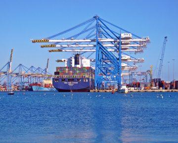 Imagem de um navio carregado com cargas em um grande porto. Ilustra ação aduaneira