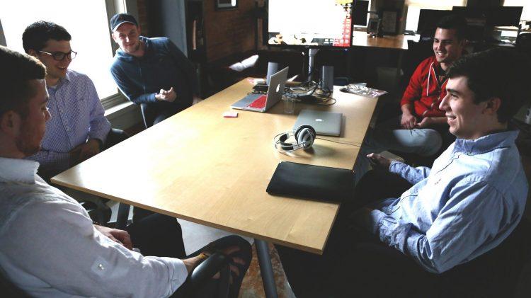 Cinco homens se reúnem ao redor de uma mesa e conversam. Parecem comentar sobre uma empresa.