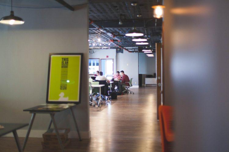 Visão distante de uma sala de reuniões, onde os participantes parecem participar de um exercício de imersão. Estão sentados ao redor da mesa.