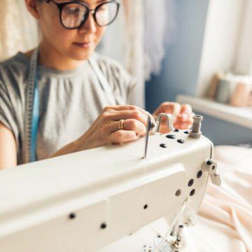 Mulher de óculos trabalha em uma máquina de costura com miçangas