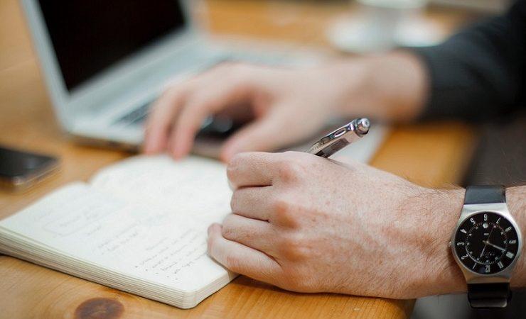 Mão masculina branca escreve em um caderno, segurando uma caneta prateada. Utiliza um relógio na mão esquerda.