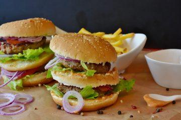 Dois sanduíches do tipo hamburguer. Cada um possui duas carnes, três pães, queijo e salada.