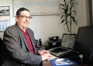 Foto de Enio Klein em frente a uma mesa, enquanto utiliza um notebook. O especialista aborda tecnologia em seu texto.