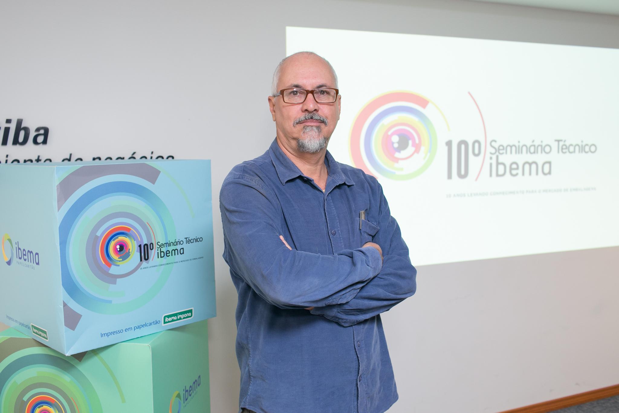 """Na imagem, o designer Fábio Mestriner está com braços cruzados em frente à uma projeção de slides onde se lê """"10º Seminário Técnico IBEMA"""", empresa onde realiza consultoria."""