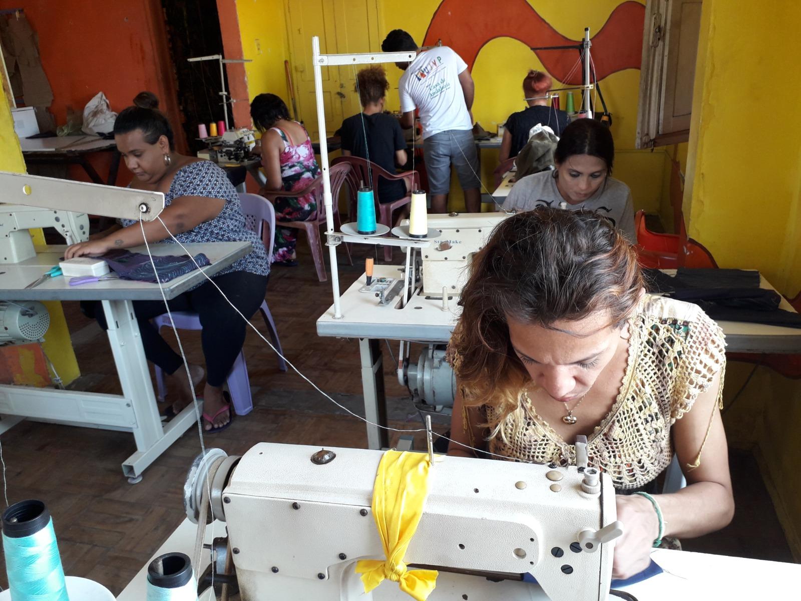 Alunas trabalham em máquinas de costura durante curso de Moda e Costura para Pessoas Trans