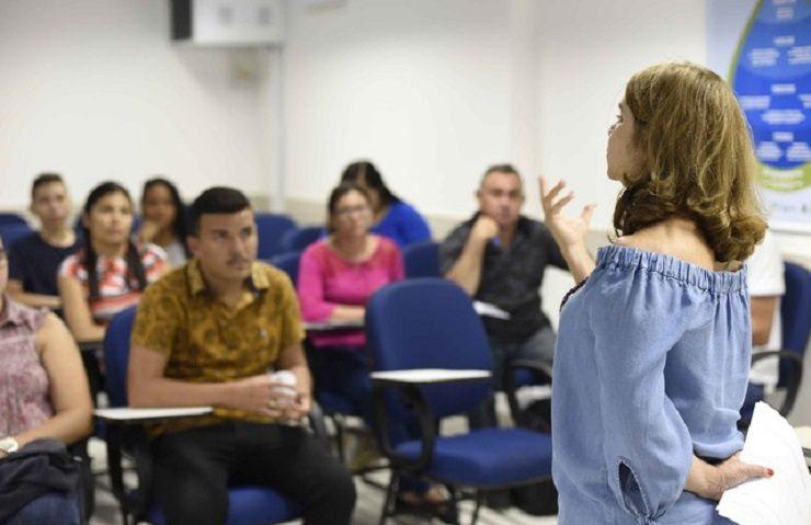 Mulher em pé ministrando aula para os alunos na Cagece, que oferta cursos profissionalizantes