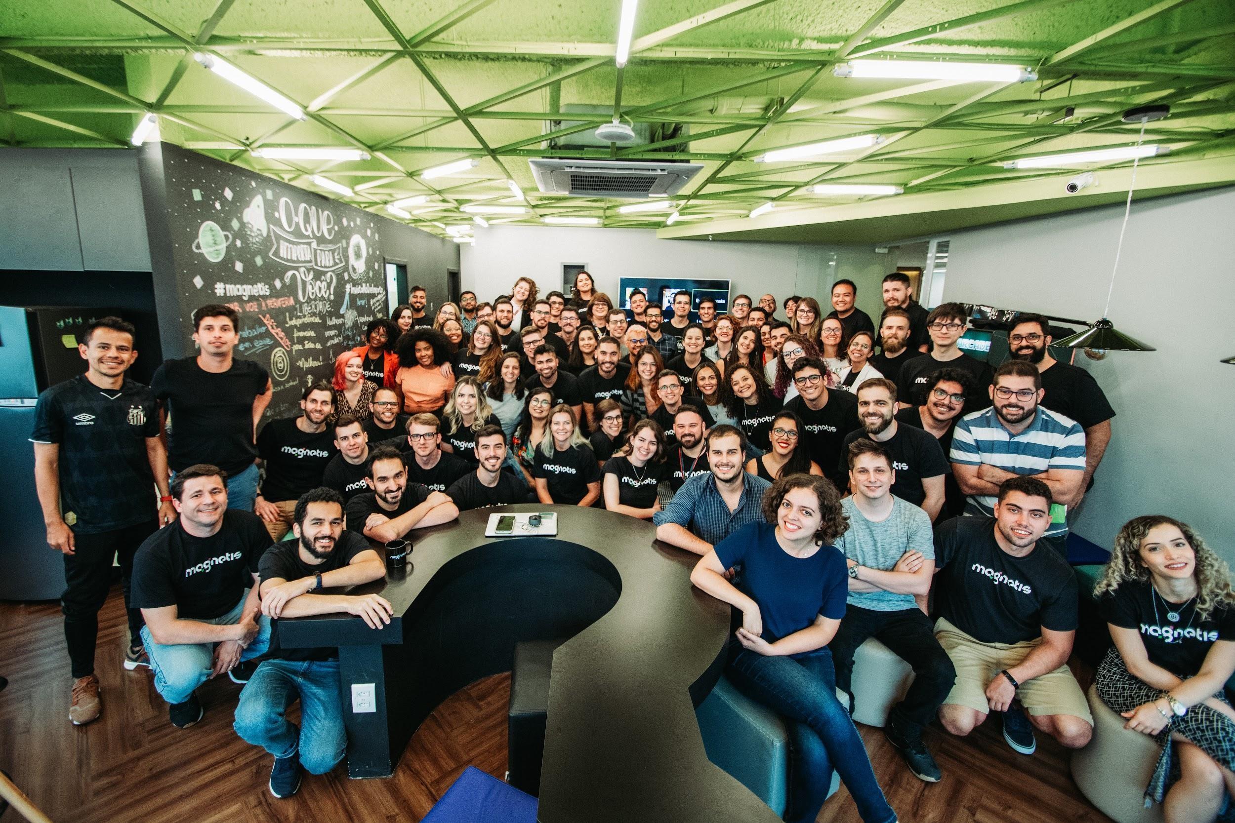 Grupo de pessoas funcionários da empresa posando para foto em uma sala ampla