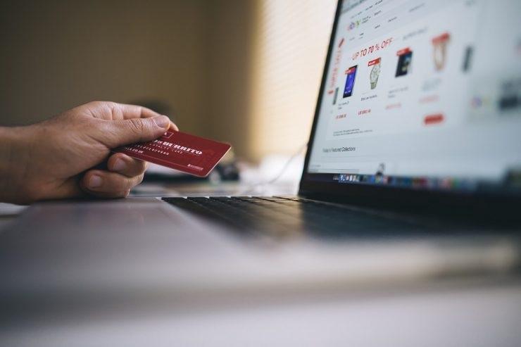 pessoa fazendo vendas pela internet. Ela segura um cartão de crédito em frente ao notebook. Ilustra o curso E-commerce na prática