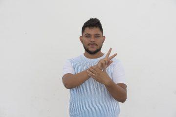 Homem falando na língua brasileira de sinais. Uece divulga edital para seleção do Semestre I do Curso de Libras Básico
