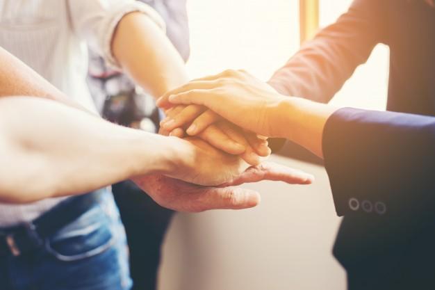 Grupo de funcionários dando as mãos, demonstrando a importância de liderar em tempos de incertezas