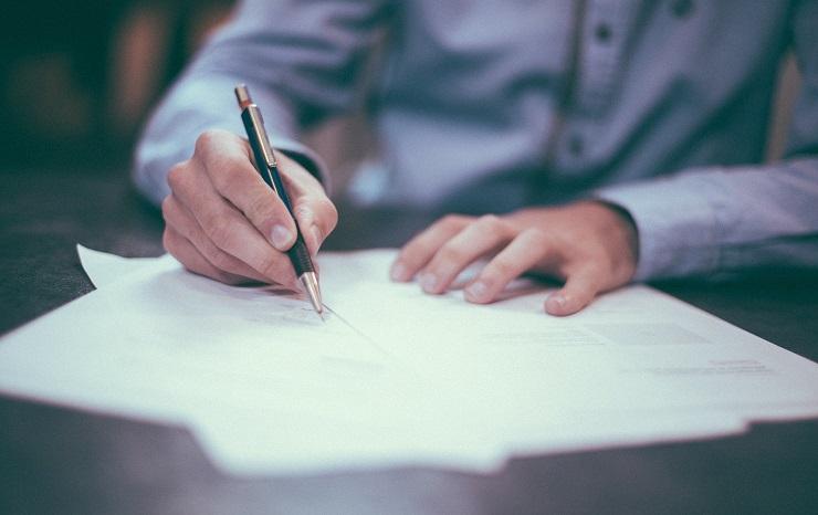 Pessoa assina um papel sobre uma mesa. Segura uma caneta preta com a mão direita. Ilustra o curso de contrato de trabalho