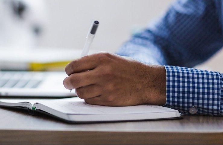 Para ilustrar o concurso público, a imagem mostra uma mão esquerda segurando uma caneta e fazendo anotações em um caderno. A manga da camisa masculina aparece e é xadrez, nas cores azul e branco.