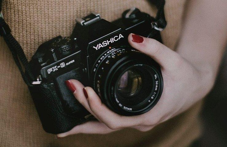 Para ilustrar os cursos da Rede Cuca, uma mão feminina com unhas pintadas de vermelho segura uma câmera analógica da marca Yashica
