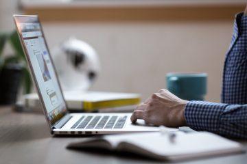 Homem utiliza um notebook. Ele traja camisa azul quadriculada. Há um livro ao seu lado. Ilustra estagiário da PGM