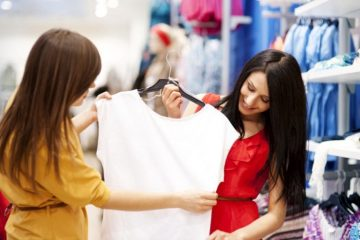 mulher segurando blusa em cabide