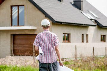 Homem com capacete segurando rolo de papel grande branco em frente a uma casa