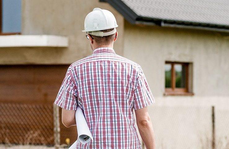 Homem de costas com capacete para construção segurando um rolo de papel branco grande com o braço esquerdo em frente a uma casa, remetendo a profissão de corretores de imóveis