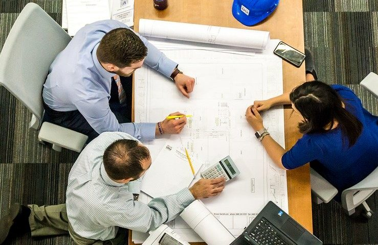 Dois arquitetos brancos e uma arquiteta branca em uma mesa decidindo um projeto; estágio na Prefeitura de Morada Nova é para as áreas de Arquitetura e Engenharia Civil