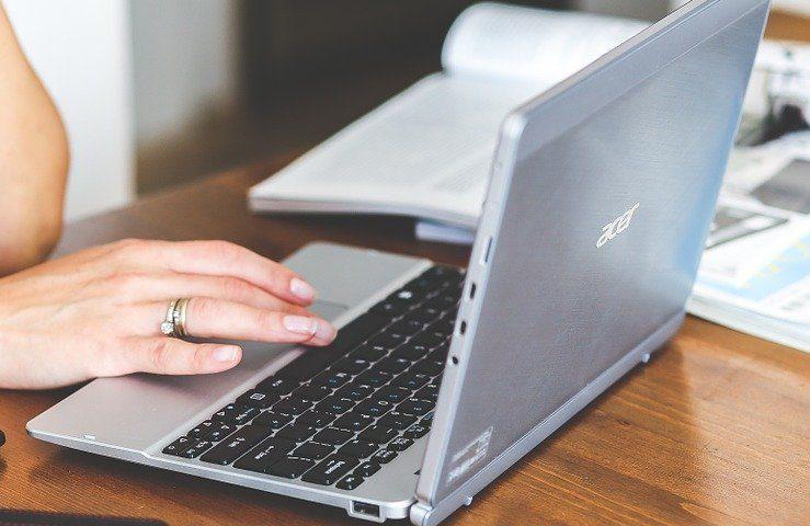 Uma mão de uma mulher com três anéis no dedo anelar teclando em um computador cinza com o teclado preto, ao fundo tem livros abertos em cima da mesa de madeira marrom que também apoia o computador