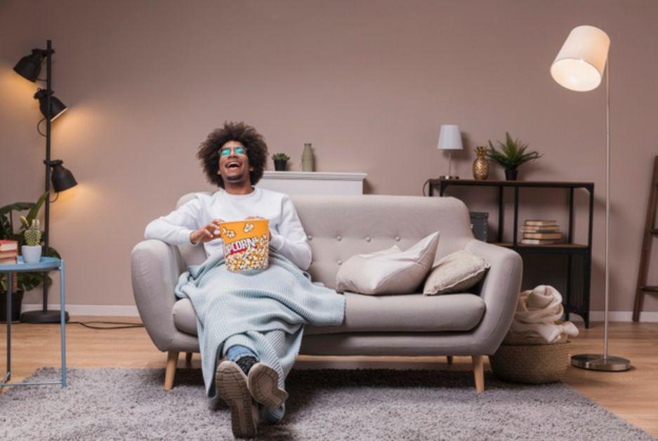 Homem sentado no sofá, com balde de pipoca no colo; especialistas do CIEE listam filmes para inspirar sua carreira