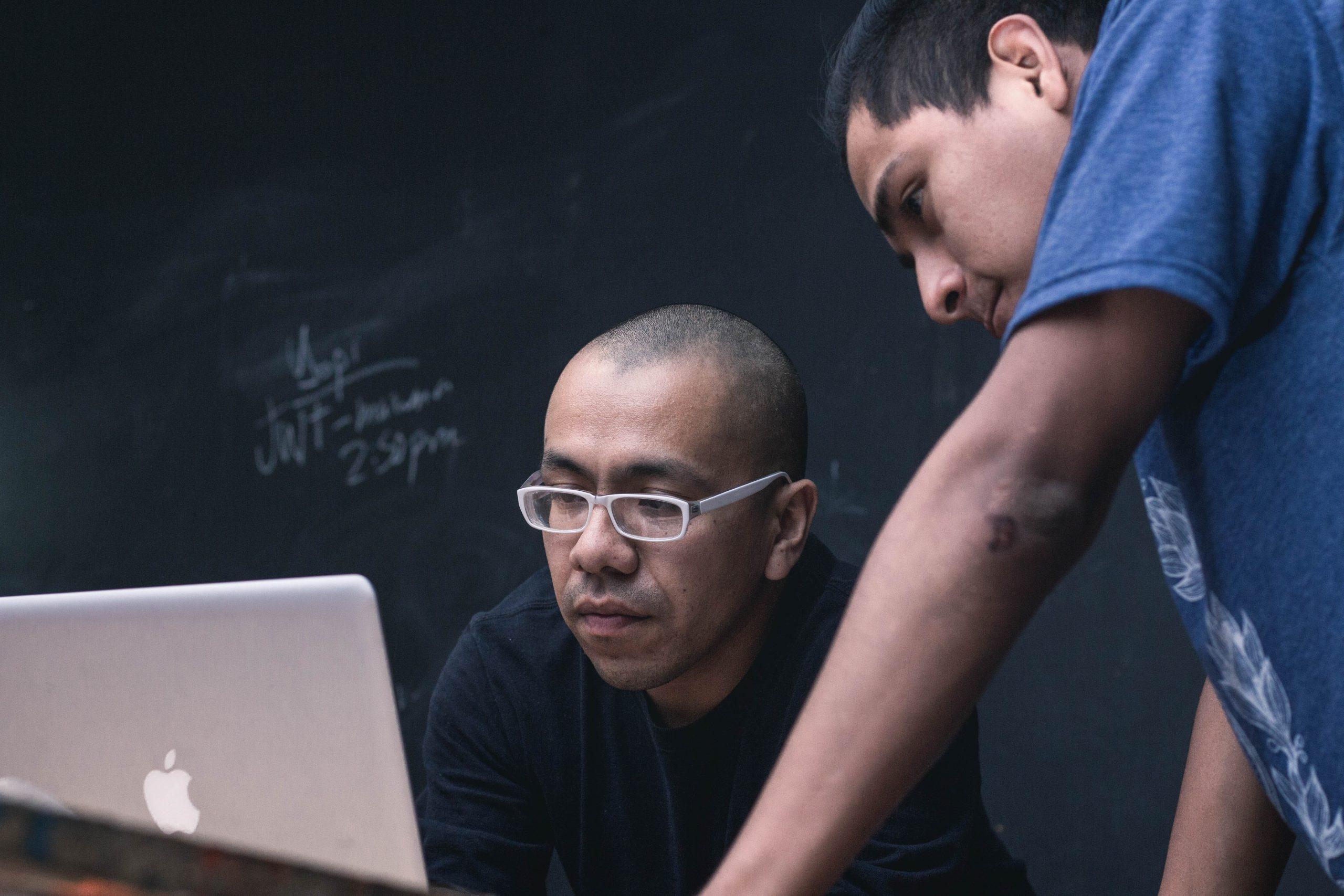 educadores em frente a um computador dentro da sala de aula