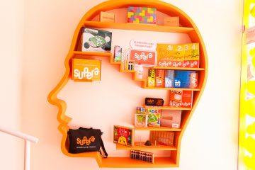 Estante em forma de cabeça humana com livros e outros produtos da marca Supera