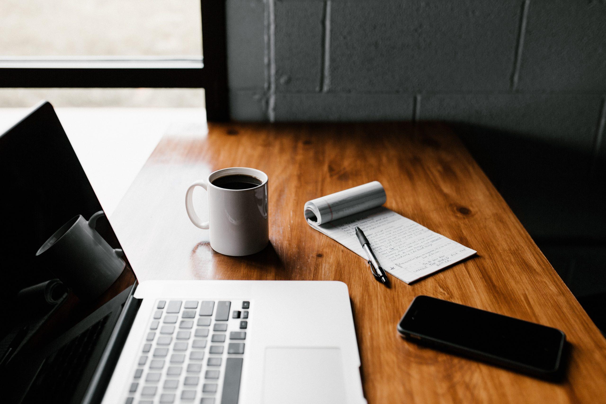 Mesa com computador, caneca de cafe, celular, bloquinho de anotações e caneta representando trabalho no home office; cuidado com as crianças e trabalho é fundamental nos tempos de Covid-19