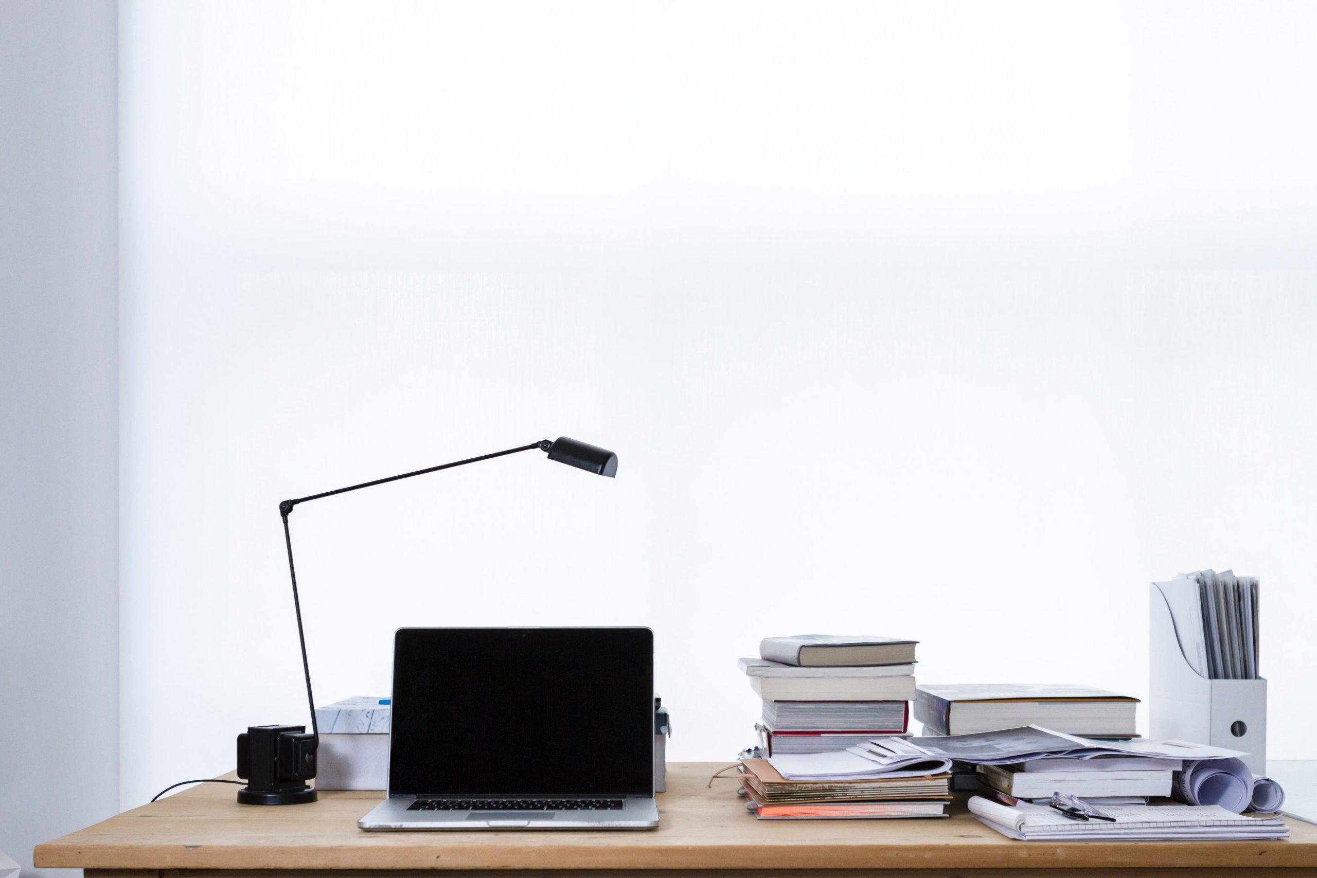 mesa de estudos com computador e livros. saiba como estudar para concursos