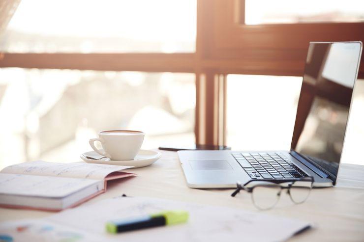 Uma mesa com notebook, livro, café e caneta; educação remota é unica alternativa possível na pandemia de Covid-19