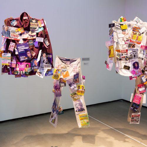 Exposição de camisas e calças com colagens de santinhos de políticos; trabalho venceu 6ª edição do Prêmio EDP nas Artes