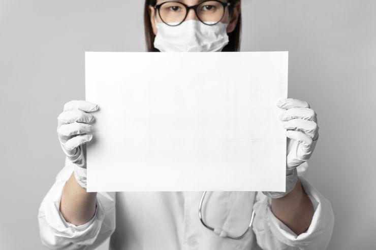 Mulher com máscara e luvas segura folha em branco que representa um mundo novo