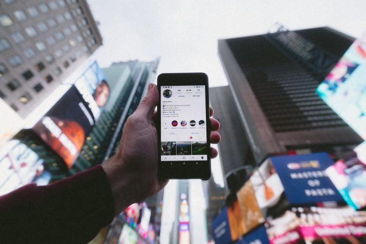 Uma mão segura um celular que está no app Instagram. Ao fundo, vários arranha-céus e propagandas que remetem a uma megalópole, provavelmente Nova York