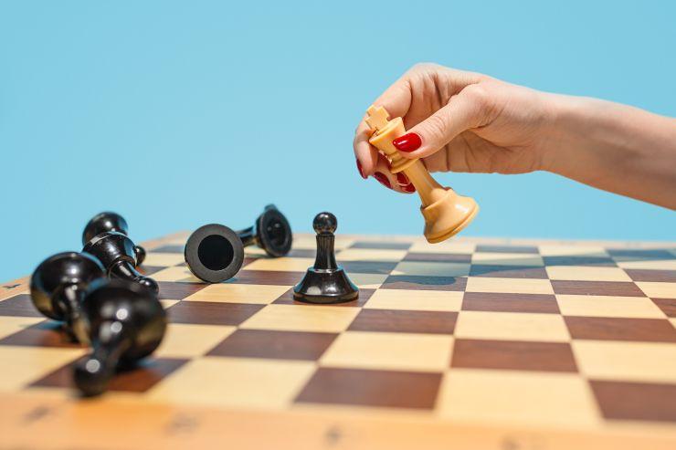 Mão feminina mexendo peça em tabuleiro de xadrez, simulando tomada de decisão e uso da inteligência emocional