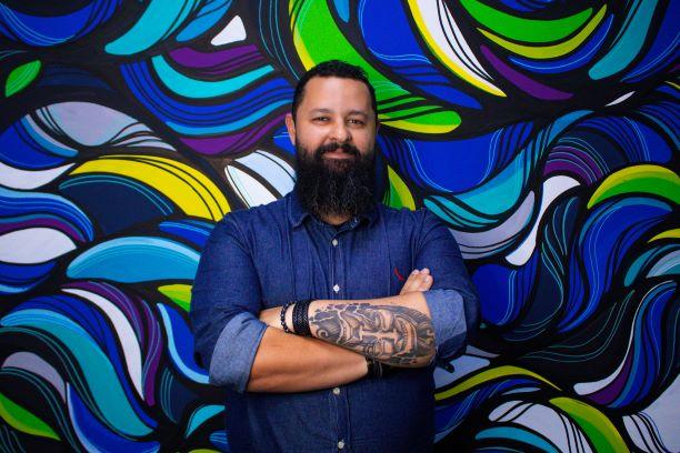 Metodologias ágeis: na foto, o especialista Danilo Vianna está de braços cruzados em frenta a uma parede com estampa nas cores azul, verde, amarelo e roxa. Em um de seus braços, há uma tatuagem grande e pulseiras pretas. Ele usa barba longa e bigode e veste uma camisa jeans de manga comprida.