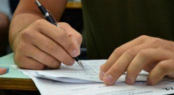 Concursos: pessoa escrevendo com caneta em uma prova