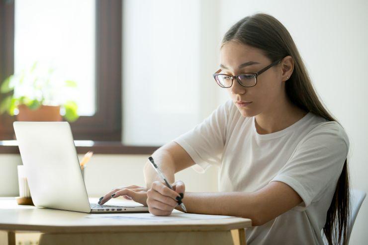 Mulher digitando em notebook e tomando no em papel; maratona de aula prepara concurseiros